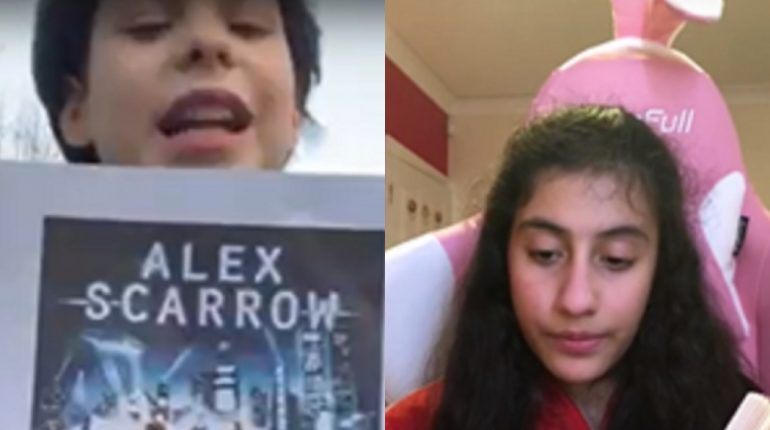 Two children on a Zoom call, one holding an image of an Alex Scarrow novel, the other sat in a big pink chair.