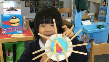 A school child holding up a piece of art they have made, a paper plate with a picture in the middle and lollipop sticks stuck around it.