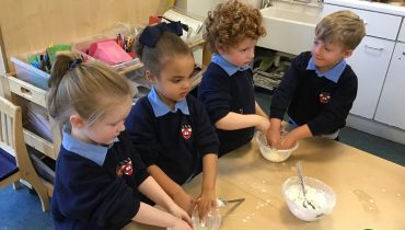 Four children at school mix dough in a bowl