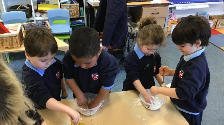 Children in school uniforms, mixing a dough in their classroom.