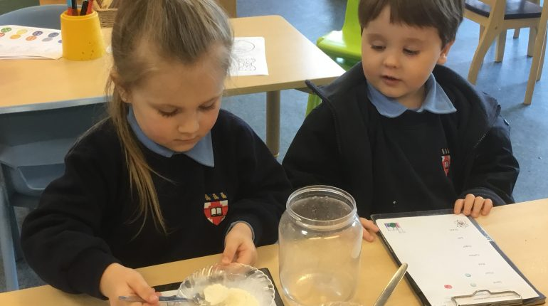 Two childrne at school in their uniforms, sat a desk with a bowl of sugar infront of them.