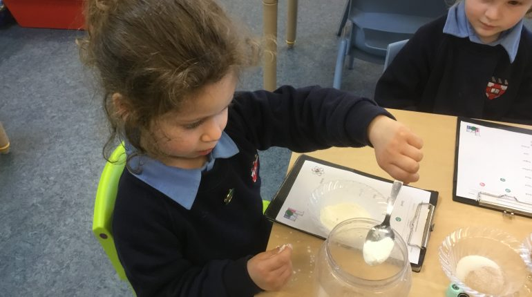 A school girl sat in a classroom spooning a white substance from a jar into a bowl.