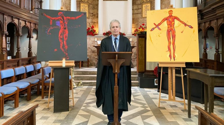 A man wearing a robe in a church, stood at podium with two pieces of art framing him on either side.