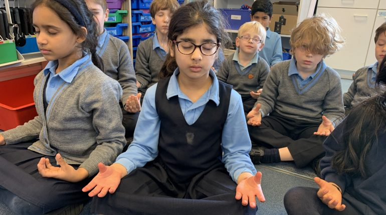 Children sat on the floor in a classroom, meditating.