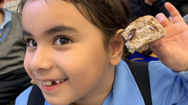 A child holding up a homemade scone.