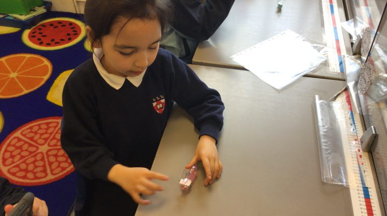 A small school girl sat at her desk playing with a pink Lego car