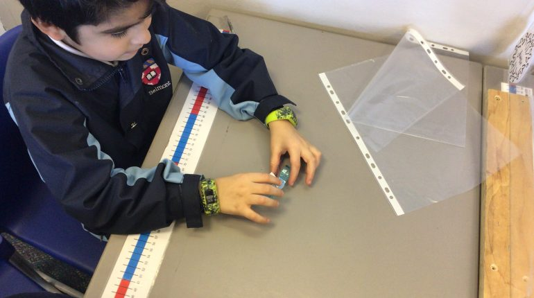 A child measuring out two rubbers.