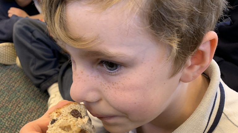 A child sat on a classroom floor, about to eat a scone.